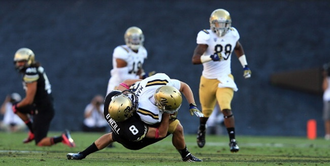 BOULDER, CO - SEPTEMBER 29:  Punter Darragh O'Neill #8 of the Colorado Buffaloes tackles running back Steven Manfro #33 of the UCLA Bruins on a punt return at Folsom Field on September 29, 2012 in Boulder, Colorado. UCLA defeated Colorado 42-14.  (Photo by Doug Pensinger/Getty Images)