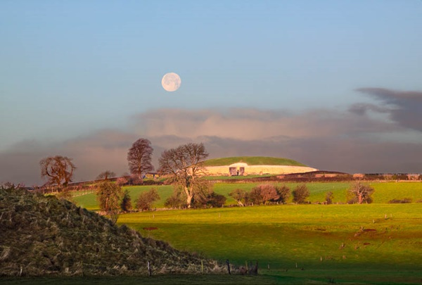 East Coast of Ireland: Meath: Newgrange. This is a view of Newgrange taken on the 3rd December 2009 at 9:00am. At this time the full moon rises before the sun sets and sets after the sun has risen - so that hunters have light for 24 hours, which is why the moon is called the Hunters' Moon. As an added bonus, the moonset was just over Newgrange, the largest and most famous Megalithic burial tomb in Ireland. In the foreground to the left can be seen a small burial tomb. For more information on Newgrange please see Newgrange.com