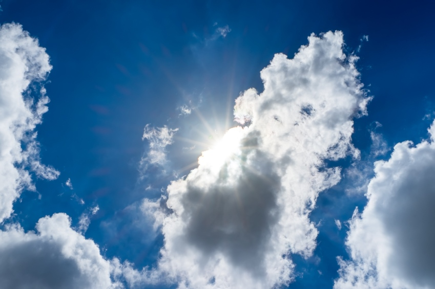 Looking up at sun ray behind cloud with blue sky.