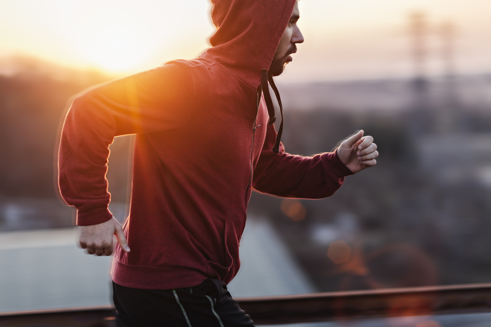 A picture of a man running and exercising beneath a clear sky, along a steal fence. He is wearing a red sweater with his hoodie pulled up and black shorts. In the distance below is some buildings and the sun is setting giving a nice warm light.