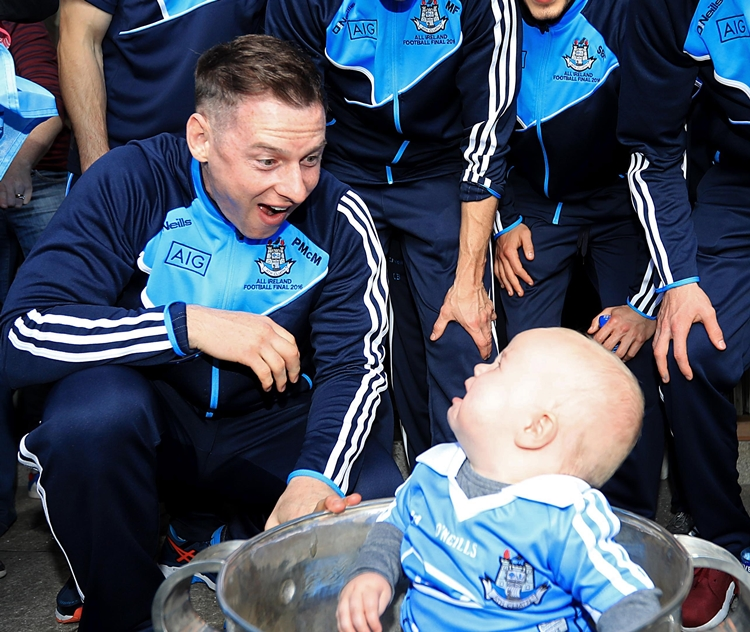 Dublin Senior Footballers Visit Crumlin Children's Hospital, Crumlin, Dublin 2/10/2016 Tomas Byrne, aged 11 months, from Dublin with The Sam Maguire trophy and Phillip McMahon Mandatory Credit ©INPHO/Donall Farmer