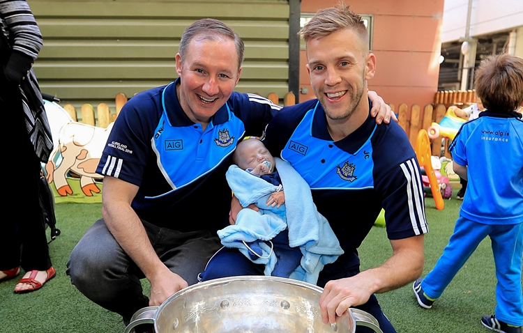 Dublin Senior Footballers Visit Crumlin Children's Hospital, Crumlin, Dublin 2/10/2016 Tom Rothwell, aged seven weeks, from Wexford with Dublin manager Jim Gavin and Jonny Cooper Mandatory Credit ©INPHO/Donall Farmer