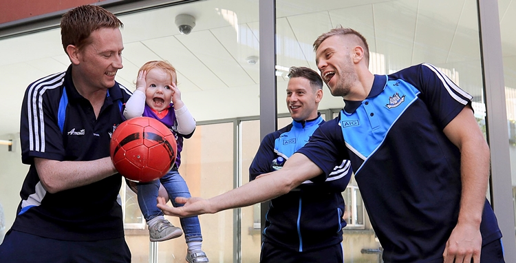 Dublin Senior Footballers Visit Crumlin Children's Hospital, Crumlin, Dublin 2/10/2016 Lucy Gannon, aged two, with Phillip McMahon and Jonny Cooper Mandatory Credit ©INPHO/Donall Farmer