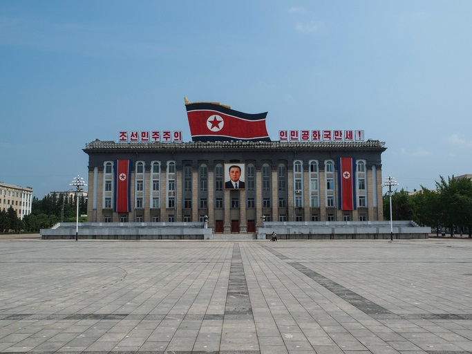 Pyongyang, North Korea – July 27, 2011: The Kim Il-Sung Square is named after the founding leader of the DPRK. It opened in August 1954. The square is located on the west bank of the Taedong River, directly opposite of the Juche Tower. The square is the common gathering place for North Korea's massive military parades. The marks on the ground serve to position the soldiers and units during these parades.