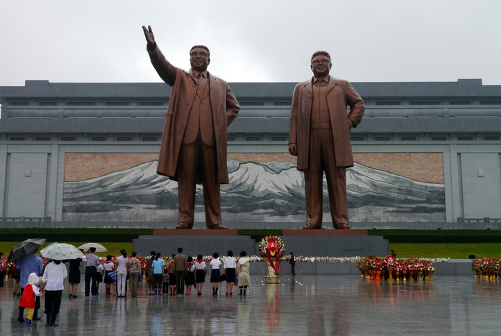 Pyongyang, North Korea - August 15 2012: North Koreans showing their respect to their political leaders at the Grand Monument on Mansu Hill with the bronze statues of Kim II Sung and Kim Jong II.