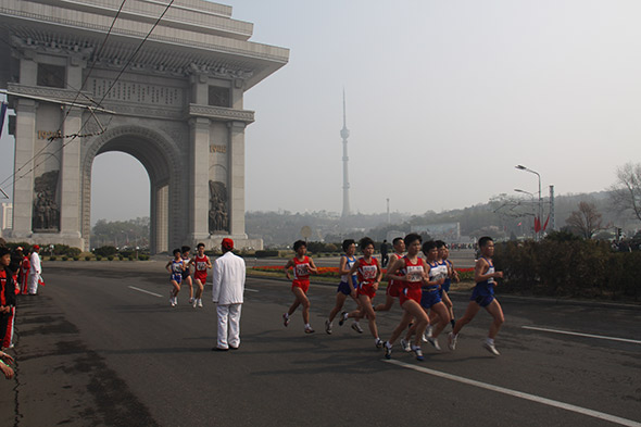 Leading Korean runners passing the 10km mark, in the background is the Arch of Triumph, built in 1982 (70th birthday of Kim Il Sung) to mark the 20 years that Kim Il Sung spent away from his home battling Japanese occupation (1925-45).